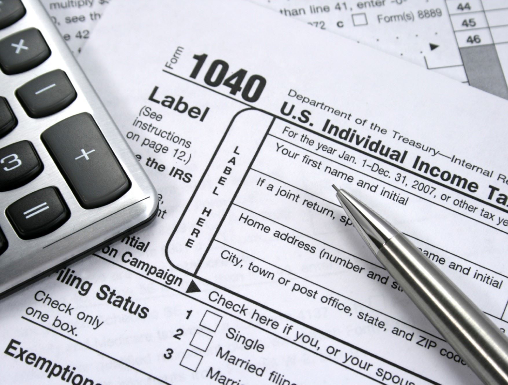 Image of income tax forms, calculator and pen