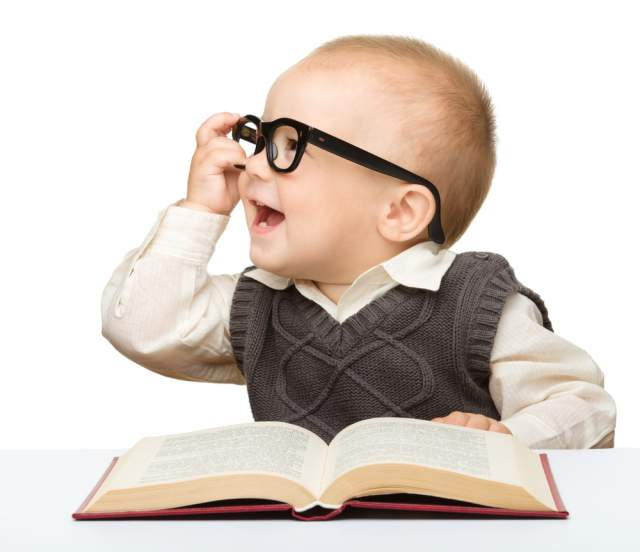 Baby wearing glasses laughs while reading a book